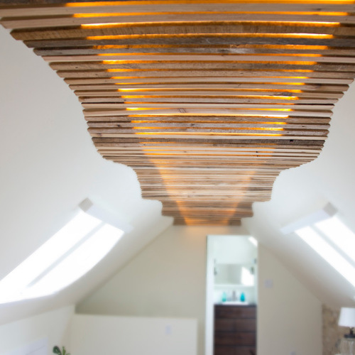 reclaimed lath wall. the 25-foot long light fixture is made of reclaimed lath boards undulating along entire length attic bedroom. source warm white wall
