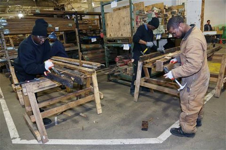 FILE - In a Feb. 28, 2013 file photo, workers at Reclaim Detroit salvage wood that was taken from abandon homes in the city and making them useful for other projects, in Detroit. Reclaim Detroit, that gives new life to wood, doors and antique fixtures salvaged from deserted homes is getting its own revival. With no strings attached, Reclaim Detroit said it has received a $100,000 grant after a fire destroyed a workshop, tools and wood saved from more than 100 houses. (Mandi Wright/Detroit Free Press via AP) DETROIT NEWS OUT; MAGS OUT; NO SALES /Detroit Free Press via AP) DETROIT NEWS OUT; TV OUT; MAGS OUT; NO SALES; MANDATORY CREDIT DETROIT FREE PRESS