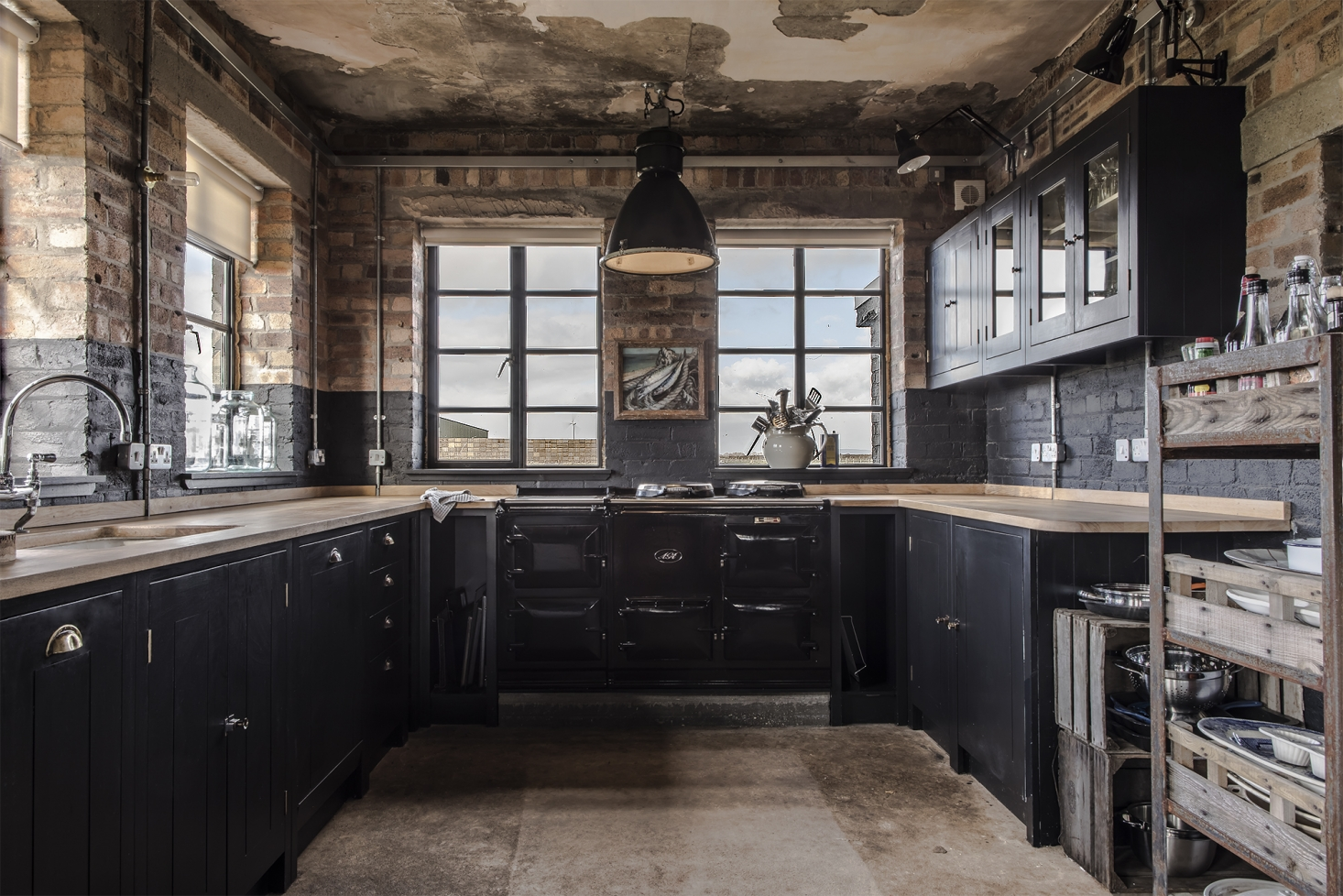 The recently installed kitchen—in what had been the officer's mess—is far from new looking. In keeping with the exterior, the couple went with a crepuscular matte charcoal for the cabinets, left the storm-ravaged brick walls exposed, and kept signs of 21st-century life largely under wraps.