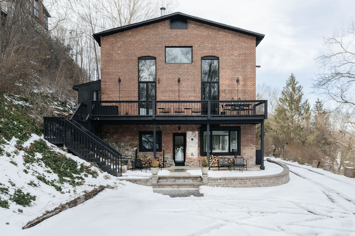 Exterior of brick house in winter with a gently pitched roof and black stairs and terrace.