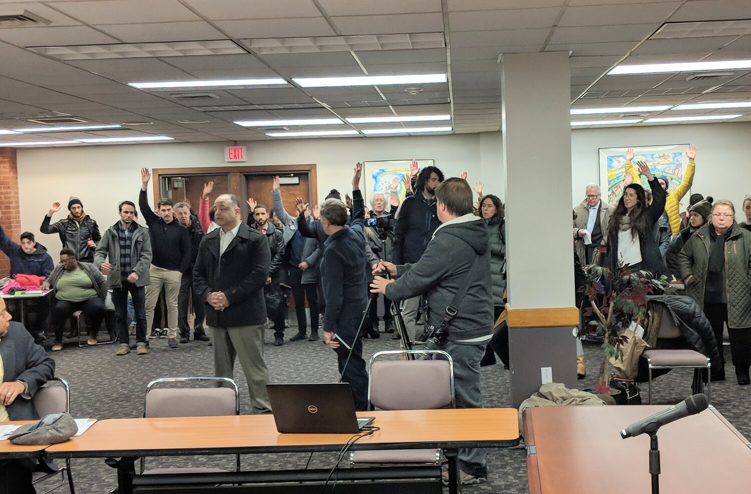 Nearly 100 opponents of the proposed waste facility on Allens Avenue in Providence raise their hands in silent protest at the Jan. 21 meeting of the City Plan Commission. (Tim Faulkner/ecoRI News)