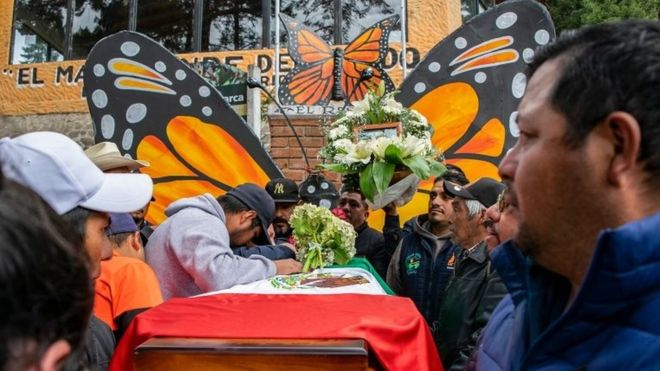 People mourn next to the coffin with the remains of environmentalist Homero Gomez