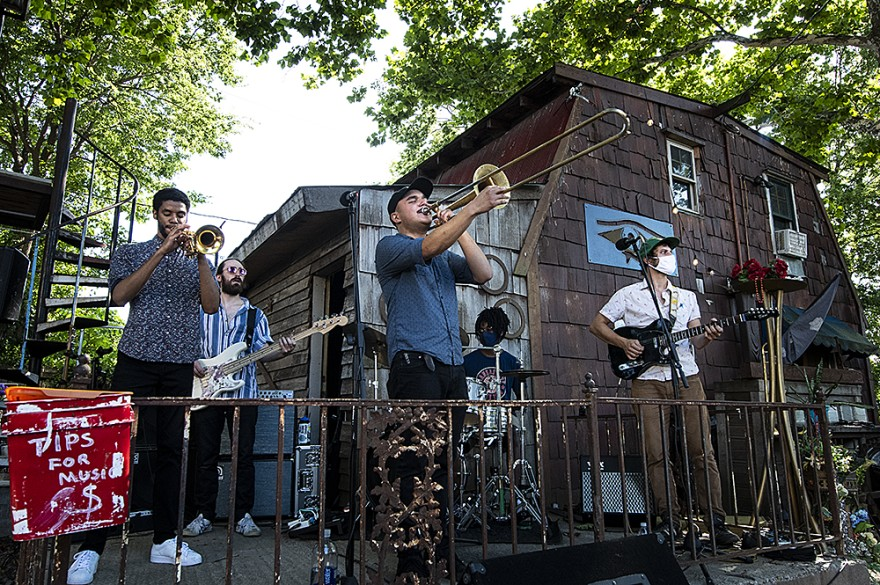 Performing on an improvised stage, trombonist Trevor Turla plays to the gathered crowd at The Raj Ma Hall, an outdoor concert venue in the Historic Northeast.